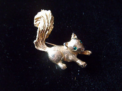 Cute little gold tone squirrel brooch with green glass eyes