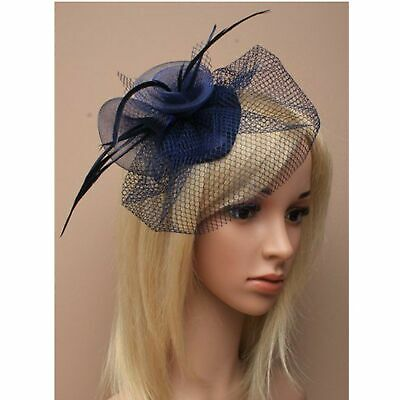 Navy blue fascinator with netting and feather tendrils and beak clip fastener.