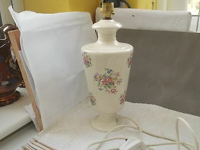 Tall, Footed Lamp Base  With A Floral Pattern On A Pale Cream Background