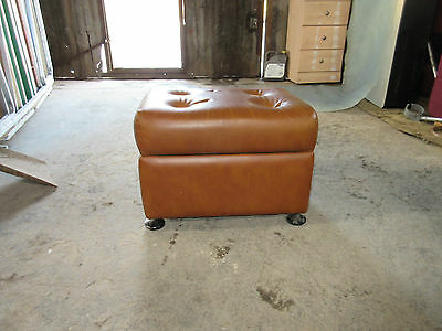 Brown leather ottoman with internal compartment.