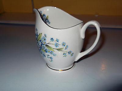Milk Jug With A Bouquet Of Small Blue Flowers As A  Pattern