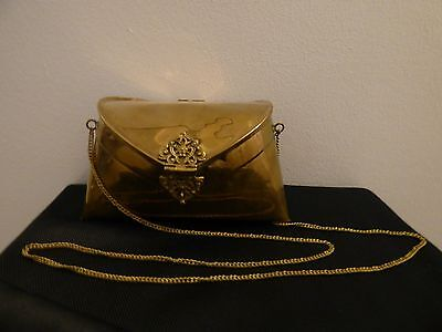 Vintage brass purse with black lining, flower and scrollwork hinges, and chain