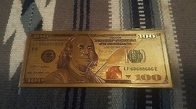 gold 100 dollar bill with protective sleeve