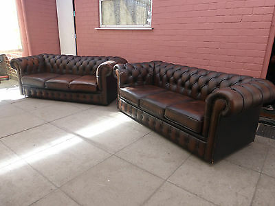 A Pair Of Brown Leather Chesterfield Three Seater Sofa Settees