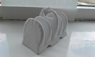 A white scallop shaped pottery toast rack
