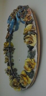 Antique mirror encrusted with porcelain flowers and bow