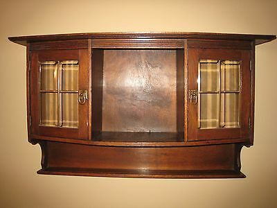 Antique hanging cabinet of solid oak with beveled glass doors