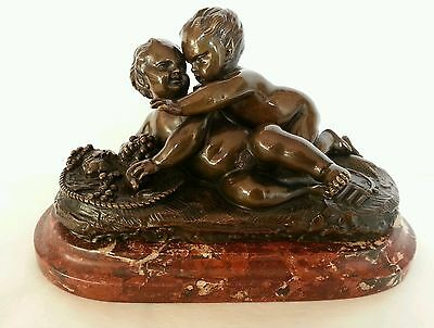 A 19th century Bronze figurine / Putti group. Raised on a Rouge Marble plinth