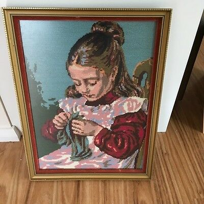 Completed Cross Stitch of girl knitting, framed