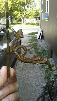 Vintage brass wall hook with a dragon hook and faces on backplate