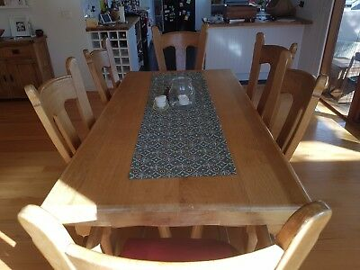 Solid oak dining table with six chairs.