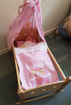 wooden rocking crib and baby doll