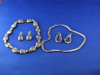 Two silver colored necklases and earrings