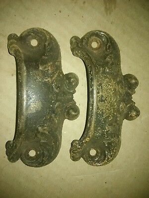 two old antique cast iron drawer pulls. very ornate