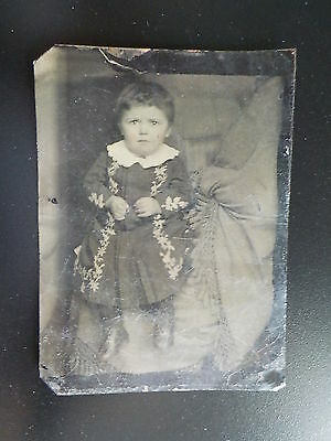 Tintype, also known as ferrotype. Pretty young girl with short hair wearing...
