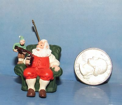 Santa Clause Enjoying Coca-Cola Be Poored by Elf