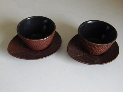 A pair of signed Japanese bronze tea bowls and saucers