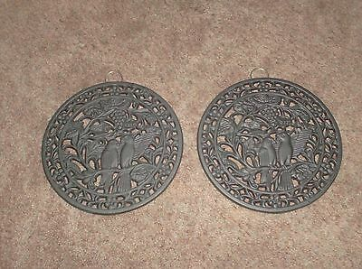 Lot 2 heavy black trivets with birds maybe parrots on them also hang on the wall