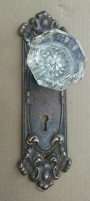 old ornate door back plate with glass knob fasten to it for coat hook