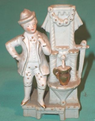antique figurine of a young man at a water well, bisque/Germany