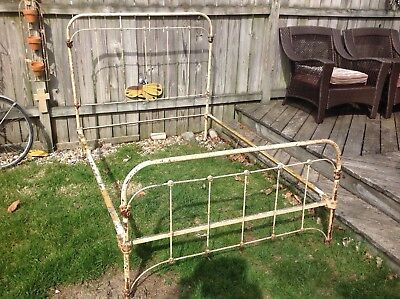 Antique Iron bed Full size with cone rails. has old chipped paint very solid