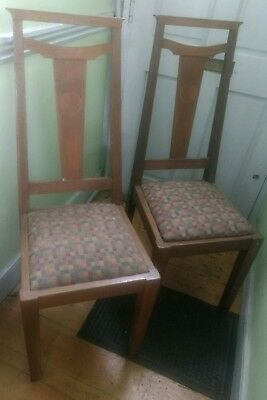 A pair of Arts and Crafts oak dining chairs