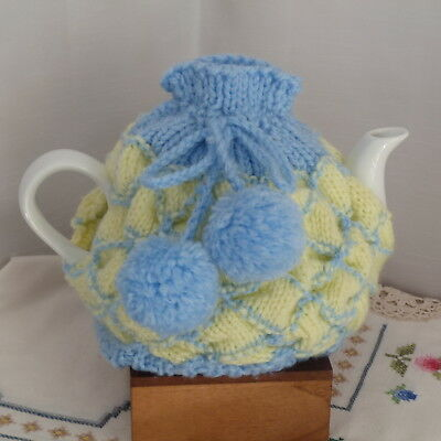 Knitted tea cosy in pale yellow and blue with pompoms
