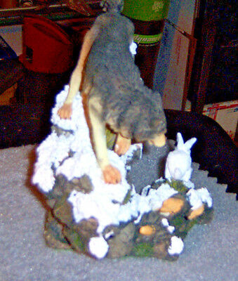 Statue Wolf chashing rabbit down a rock mountain covered with snow