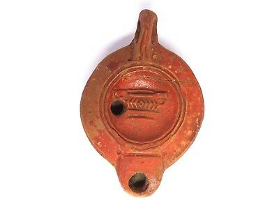 Ancient roman oil lamp depicting two handled cup