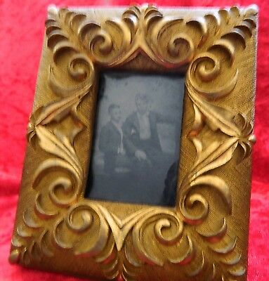 Daguerreotype of one man on the lap of the other with gilt frame