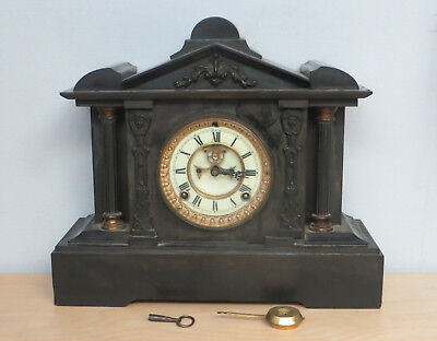A Victorian black slate mantel clock with visible escapement & two train mvmt