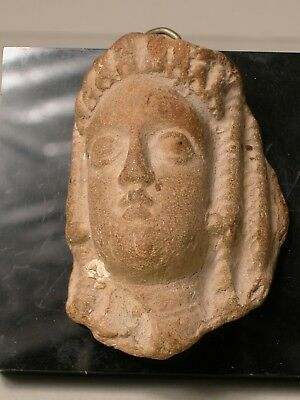 a small hellenic stone face of a woman (kore)