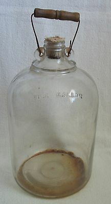 antique full gallon glass jug with wood handle and cork