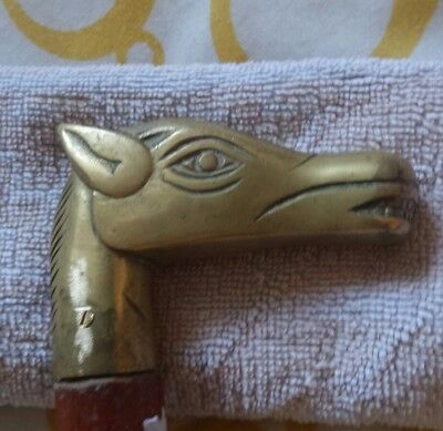 Vintage walking stick with brass horses head. And souvenier badges from visits.
