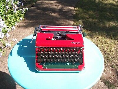 beautiful red Olympia portable typewriter and case.