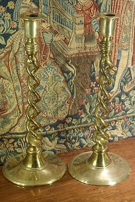 An Antique Pair Of Usual Design Round Based Brass Candlesticks