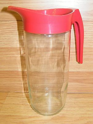 "Unbranded (L-170A) 8"" Tall x 3 1/2"" Wide Glass Pitcher With a Red Handle & Spout"