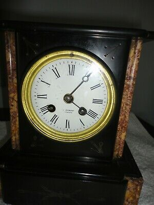 Small striking mantel clock in black slate/marble. Good working order .