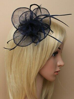 Navy blue fascinator with simulated flower and feather tendrils on clip and pin.