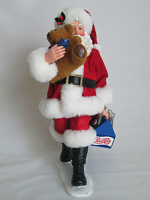 Santa Claus figure holding a teddy bear and Pepsi cola bottles in a case