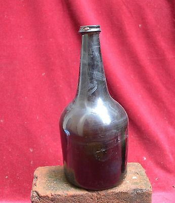 Authentic 18th century dark green glass free blown wine bottle.