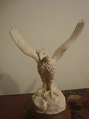 lovely sculpture in cream porcelain of eagle with open wings on brown wooden pli