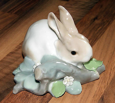 Lladro rabbit figurine, rabbit sat on a log eating a flower.
