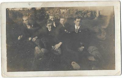 Photo   Of  A  Group  Of   Young   Men  Sitting  In   A  Field.
