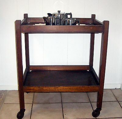 Vintage solid wood two tier tea or drinks trolley with metal caster wheels.
