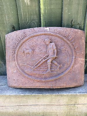 A antique cast iron plaque depicting a horse drawn plough