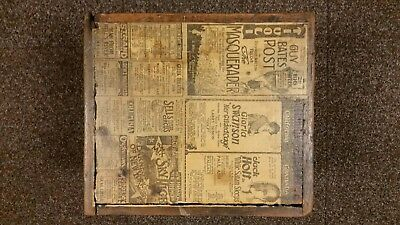Antique wood box with old news paper advertisements on it.