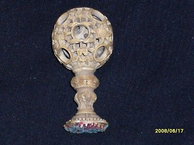 a small antique chinese puzzle ball on a stand