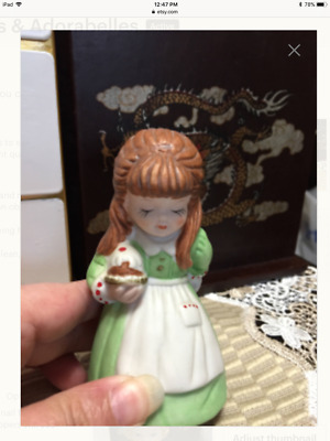 Little girl in green holding Christmas Pudding Bell