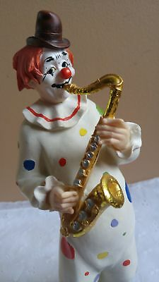 Clown with a golden saxophone figurine